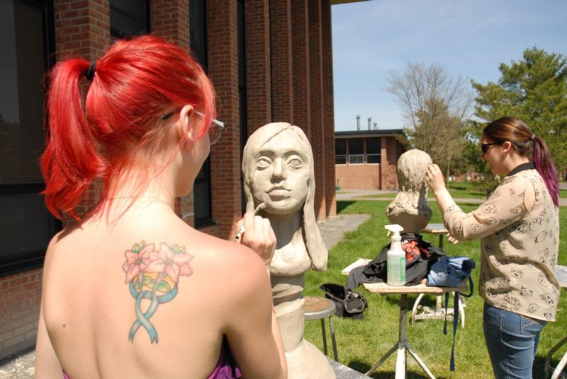 students working on sculpture projects outside