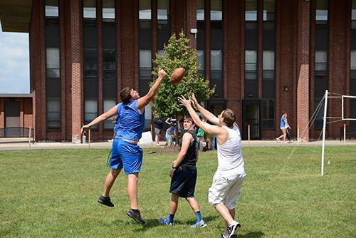students playing football in front of dorms