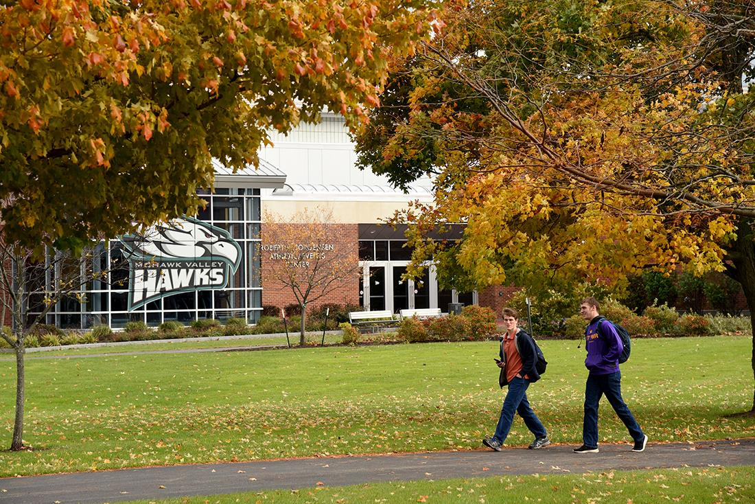 Two students walk under fall foliage during autumn at the Utica Campus