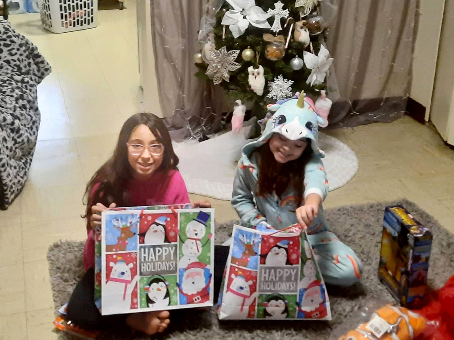 Children smiling, holding the gifts they received from Kidz N Coaches.